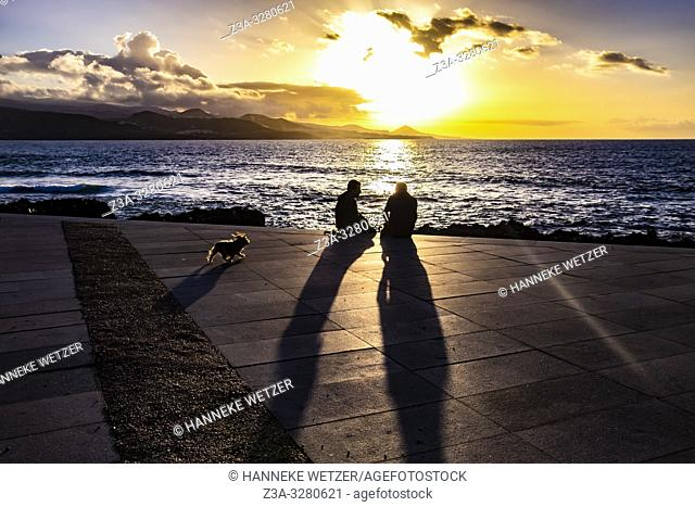 Two men and a dog enjoying the sunset at the coastline of Las Palmas de Gran Canaria, Canary Islands