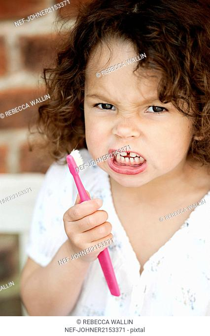 Angry girl holding toothbrush