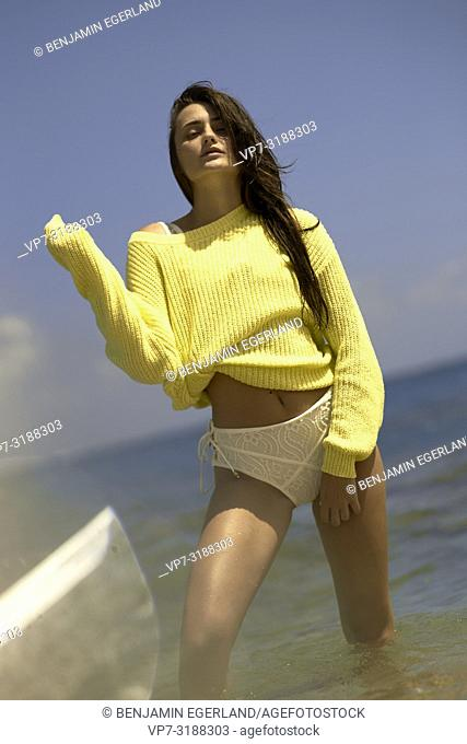 Young woman at beach in a yellow sweater. Crete, Greece