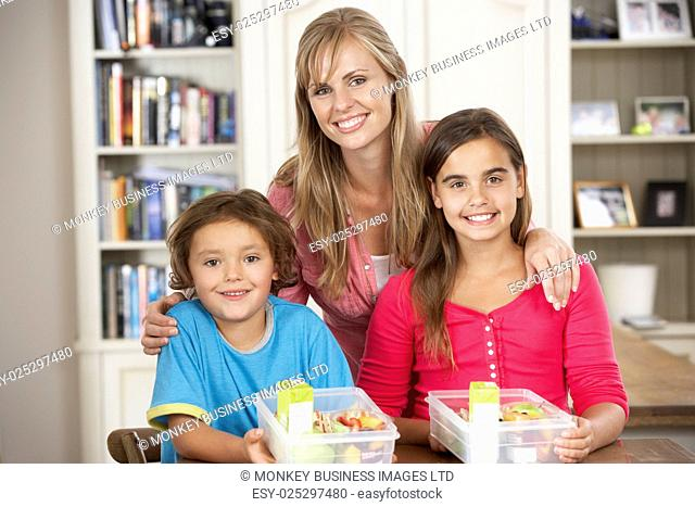 Mother Giving Two Children Healthy Lunchboxes In Kitchen