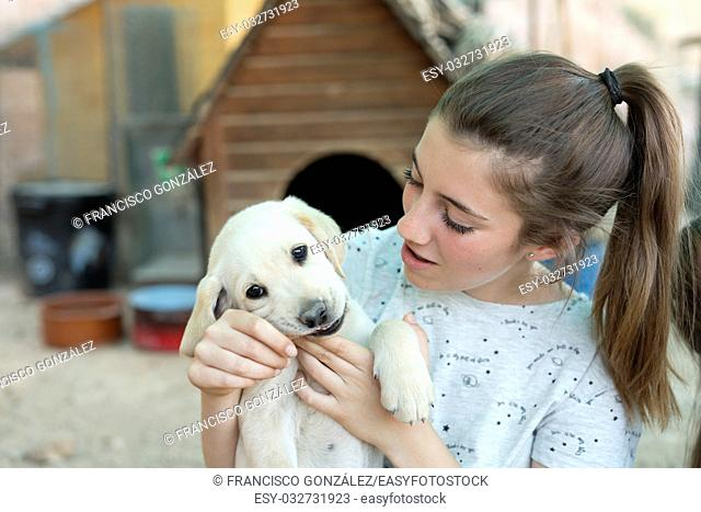 Portrait of a teenage girl with a golden retriever puppy