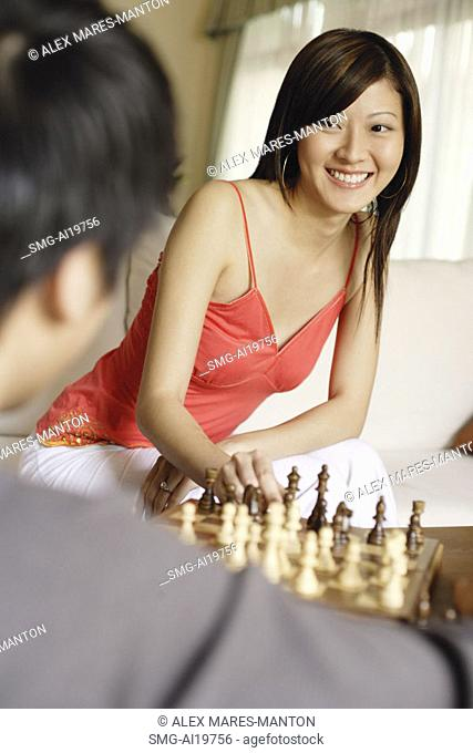 Couple in living room, playing chess