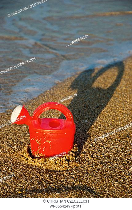 Watering can at the beach