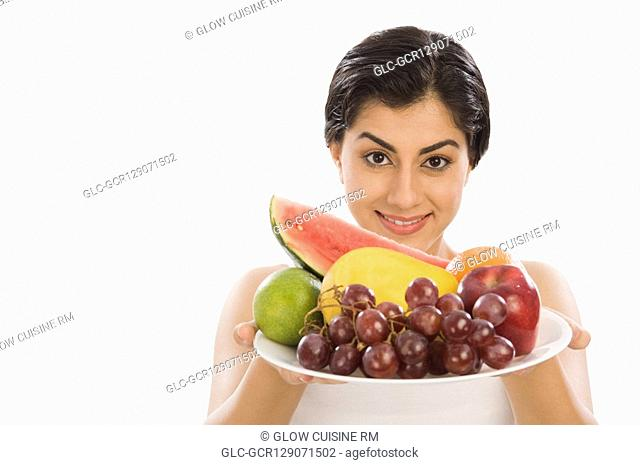 Portrait of a woman holding a plate of assorted fruits