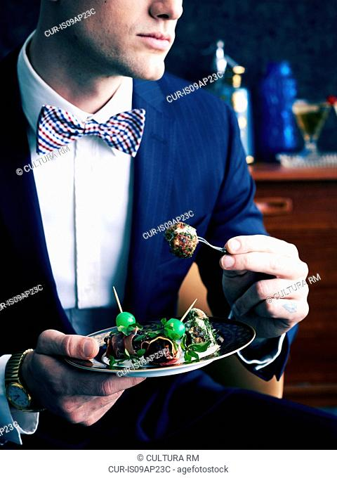 Retro styled man eating plate of appetizers
