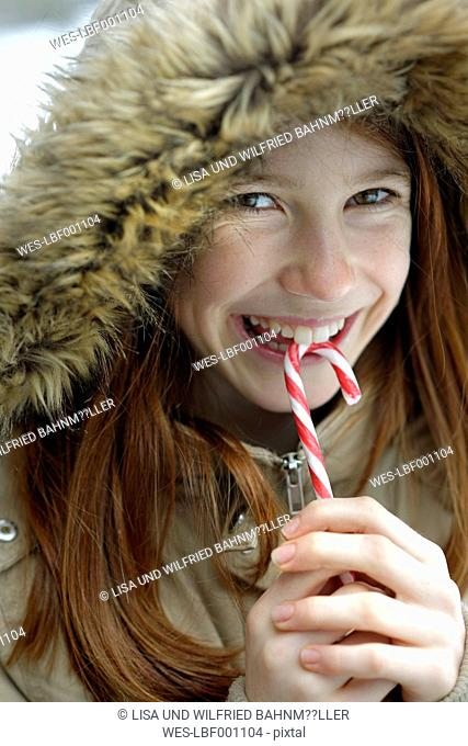 Portrait of happy girl holding candy cane