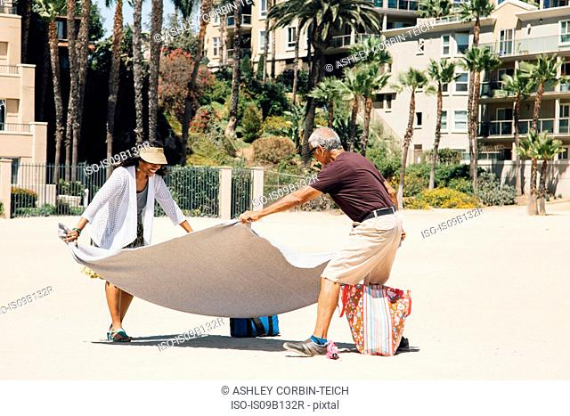 Senior couple on beach, laying out blanket for picnic, Long Beach, California, USA