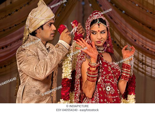 Indian groom trying to put a garland on his bride