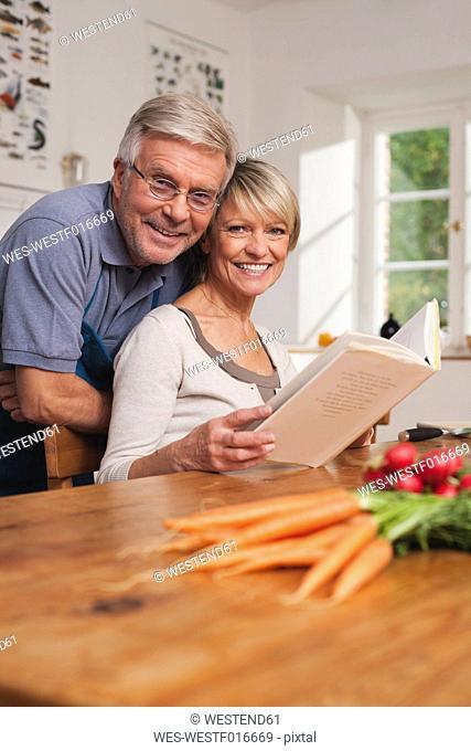 Germany, Kratzeburg, Senior couple preparing food from cook book