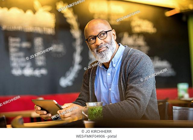 Portrait of man with tablet in a coffee shop