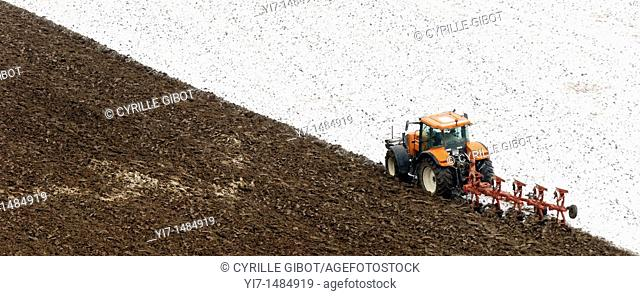 Tractor ploughing snowy field, Saint-Floret, Auvergne, France