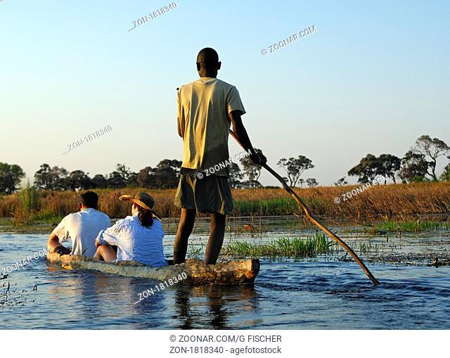 Kahnfahrer mit Touristen im traditionellen Mokoro Einbaum auf Exkursion im Okavango Delta, Botswana / Poler with tourists in a traditional mokoro logboat on...