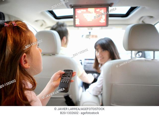 Family travelling, girl watching DVD in car