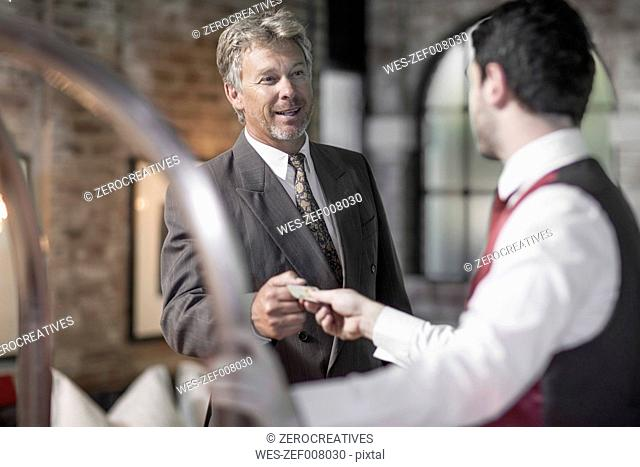 Man in hotel room with bellboy