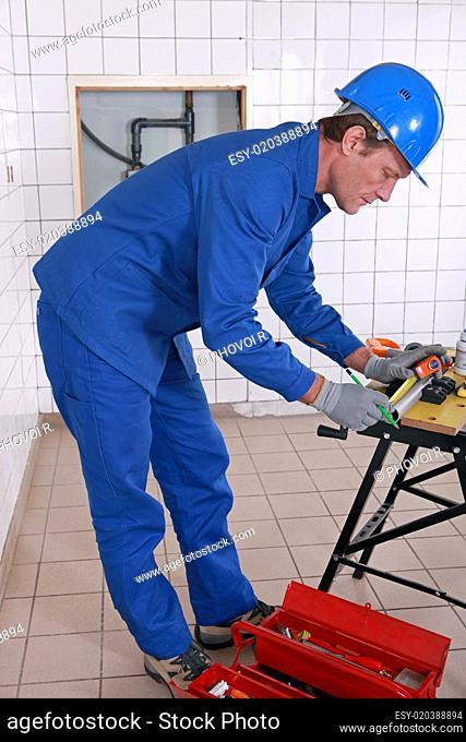 Plumber measuring plastic pipe