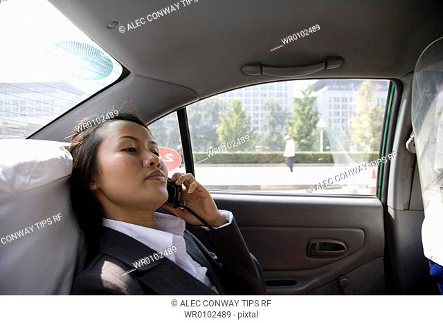 Asian woman in car on mobile