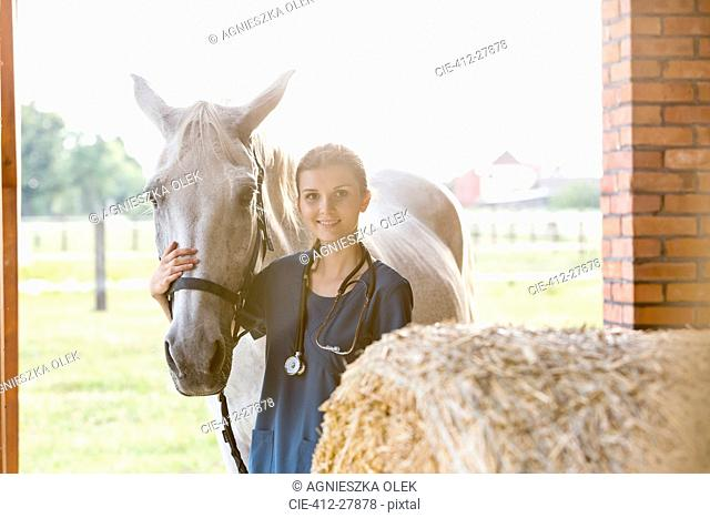 Portrait smiling veterinarian with horse in barn