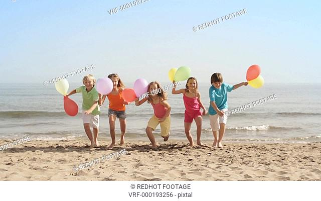 Slow motion of five children running towards camera on beach holding balloons