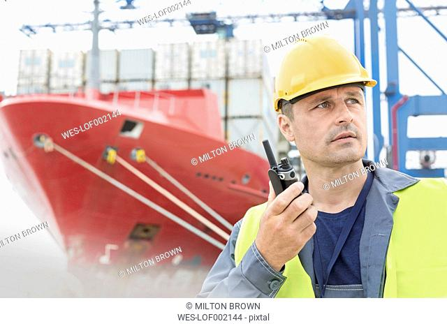 Man with walkie-talkie at container port
