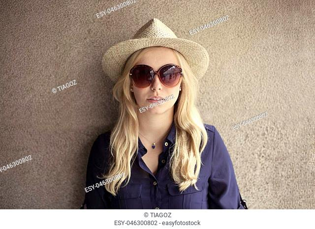 Blonde woman with straw hat in front of a wall