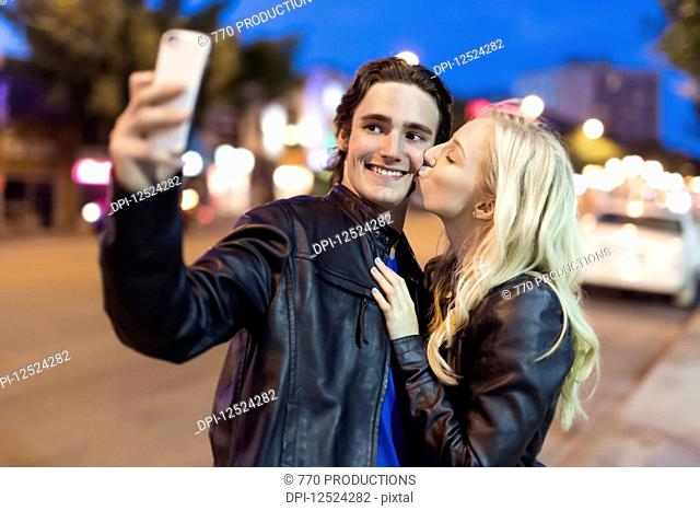 A young couple take a self-portrait with a smart phone as the female kisses the male on the cheek along a street at dusk; Edmonton, Alberta, Canada