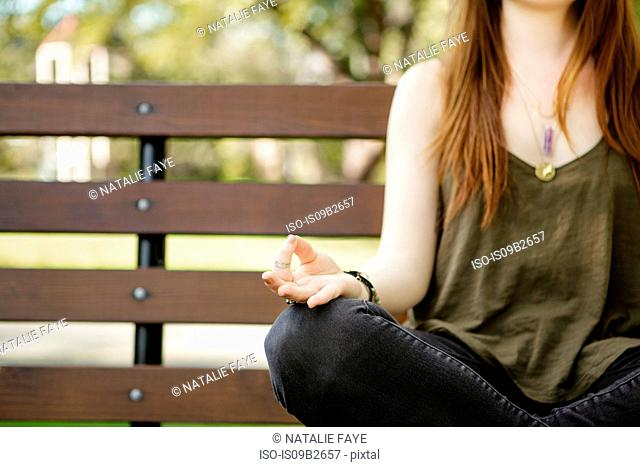 Neck down of young woman practicing lotus yoga position on park bench