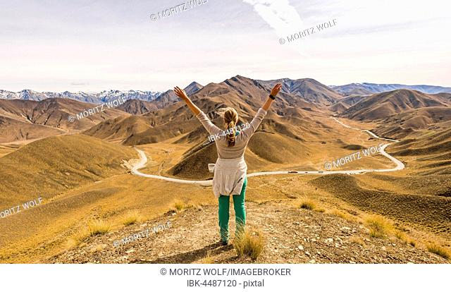 Woman looking at stark mountain landscape with mountain road, Lindis Pass, Southern Alps, Otago, Southland, New Zealand