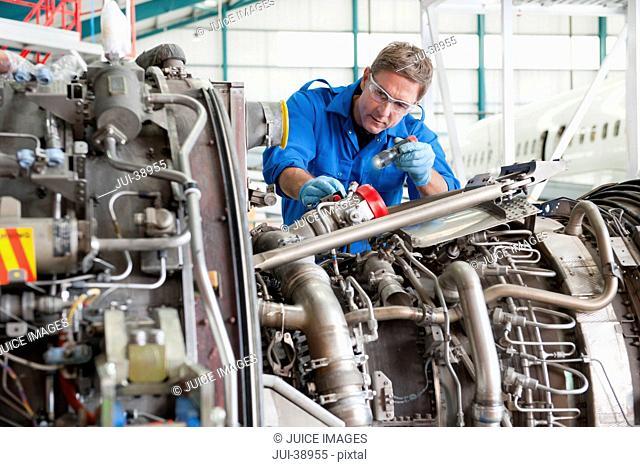 Engineer inspecting engine of passenger jet in hangar