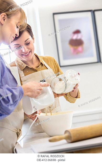 Women baking, using electric hand mixer in kitchen
