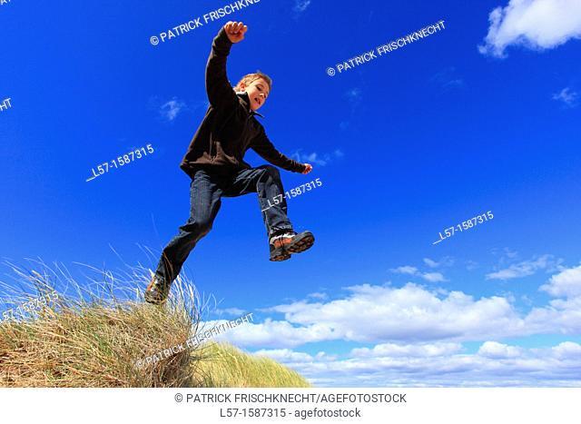 boy jumping from dunes Sutherland, Scotland
