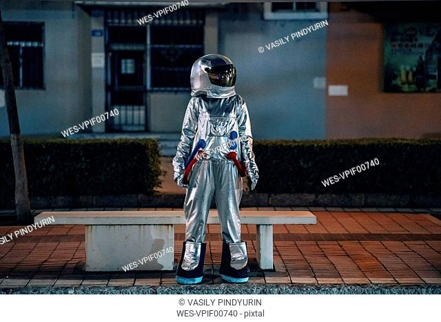 Spaceman standing at a bench in the city at night