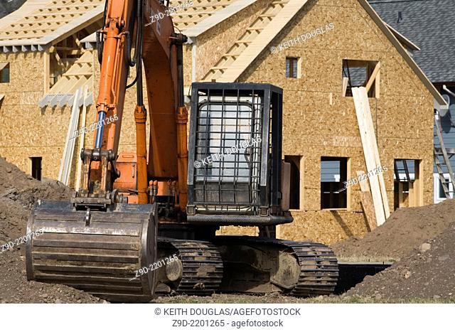 Excavator and new homes at subdivision, Smithers, BC