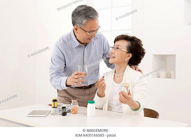 Senior couple eating medicine and looking at each other with smile