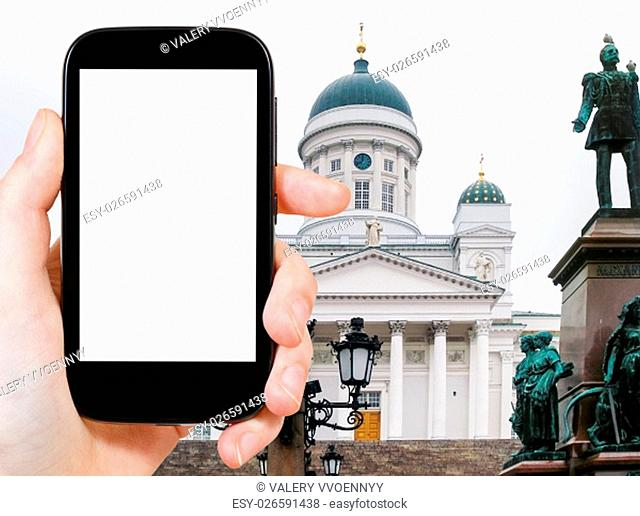 travel concept - tourist photographs Cathedral in Helsinki Finland (St Nicholas Church) on smartphone with cut out screen with blank place for advertising