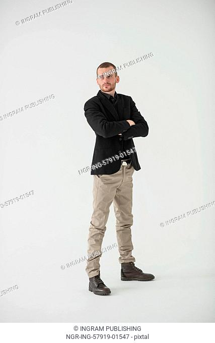 Happy businessman standing with arms folded on white background, natural light