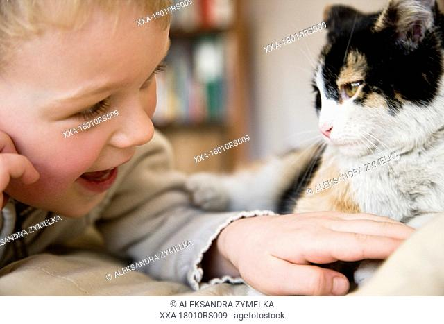 boy playing with cat on bed