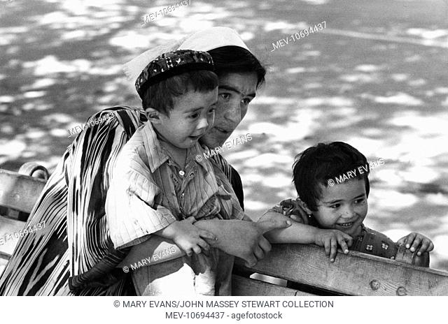 An Uzbek woman and two children, on a bench in a square in Tashkent, then in Soviet Russia, now in Uzbekistan, Central Asia