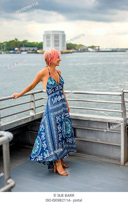 Mature woman standing on boat, looking at view, smiling