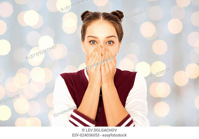 people, emotion, expression and teens concept - scared or confused teenage girl over holidays lights background