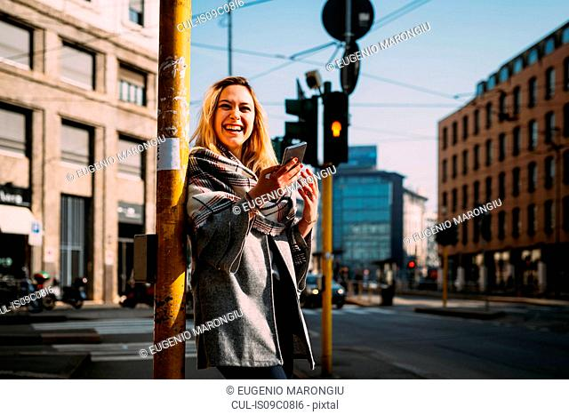 Young woman with smartphone laughing at tram station, Milan, Italy