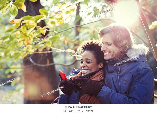 Smiling couple using cell phone in sunny autumn park