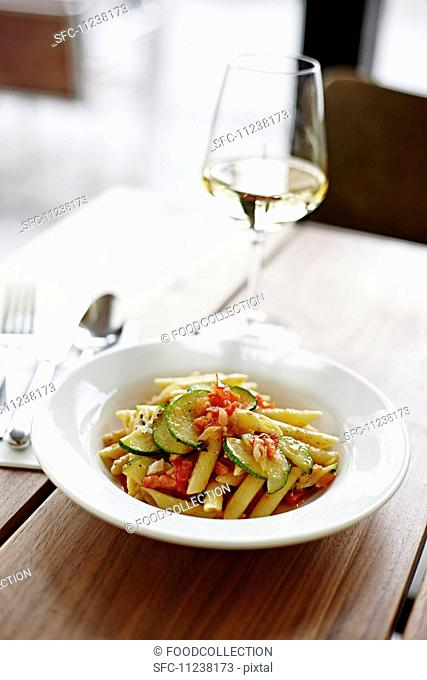 Penne with tomatoes and courgette, with a glass of white wine