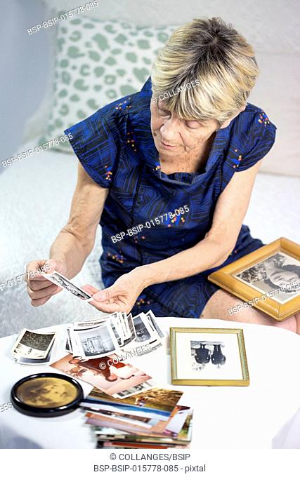 Old woman looking at photos