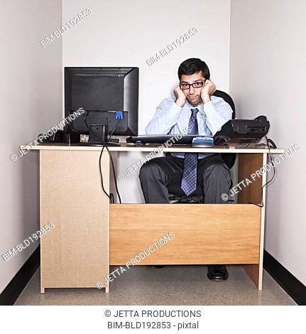 Hispanic businessman working in small office