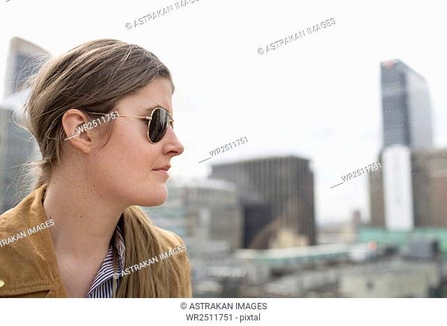 Close-up side view of businesswoman wearing sunglasses standing against buildings