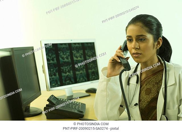 Female doctor examining an X-Ray and talking on the telephone