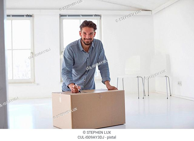 Portrait of young man writing on cardboard box whilst moving house