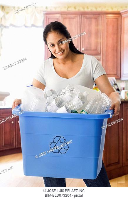 Hispanic woman carrying bin of recyclable bottles