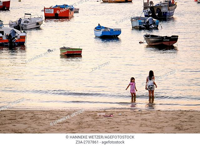 Two kids playing at the beach of Trafaria, Portugal, Europe