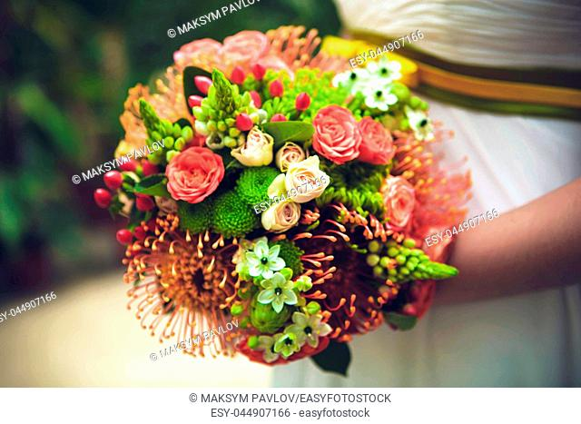 Bride with bouquet from different flowers. Close up